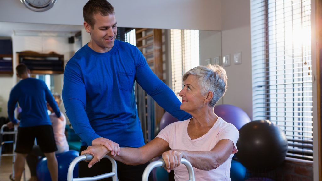 Physiotherapist assisting senior woman patient to walk with walking frame