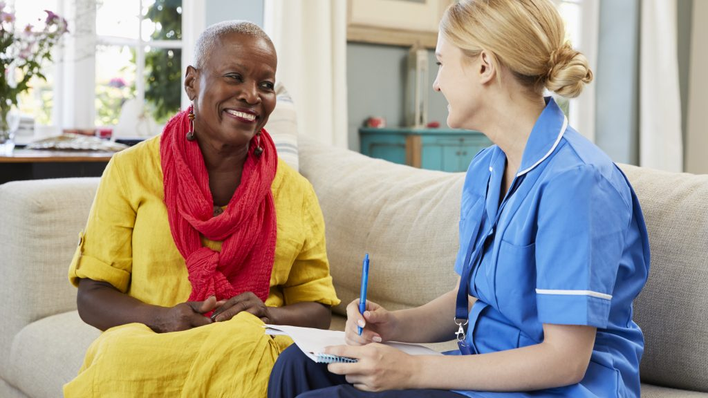 Female Community Nurse Visits Senior Woman At Home