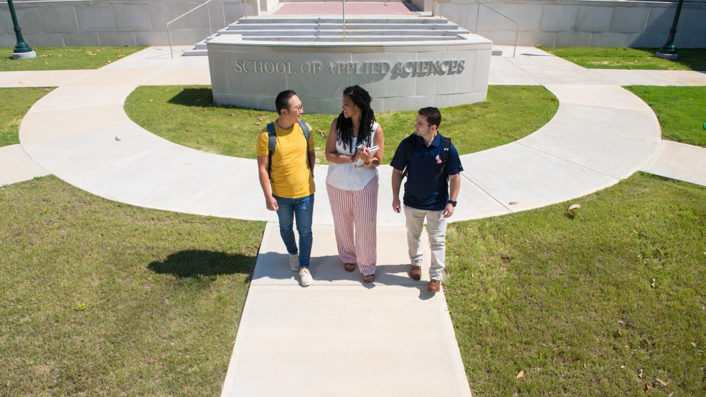Three students gather in front of the new Applied Sciences building